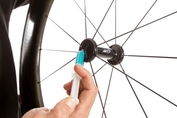 We apply a thin layer of CeramicSpeed's blue grease on the outside of every new bearing and every hub's recess where the bearing fits into